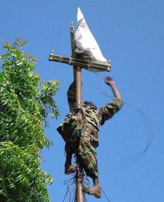 TFG soldier replacing al-Shabaab flag in Bakara