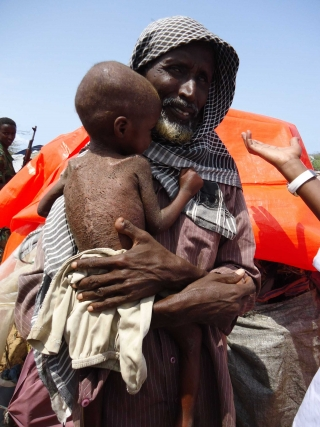 A famine-hit child clutches its father